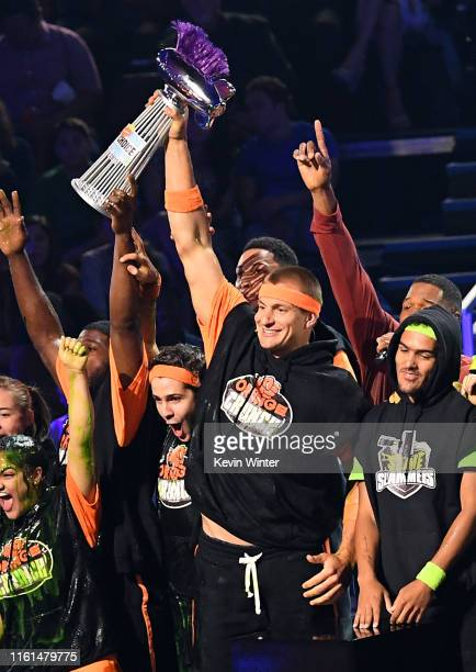 Laurie Hernandez P K Subban David Dobrik Rob Gronkowski accept a trophy after winning a challenge while Trae Young looks on onstage during...
