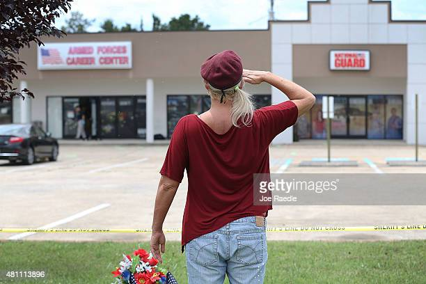 Laurie Norman salutes in front of the Armed Forces Career Center/National Guard Recruitment Office which had been shot up as she pays her respects to...