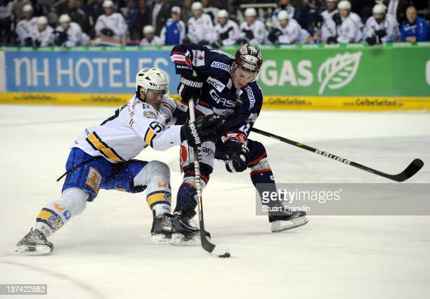 Laurin Braun of Berlin is challenged by David Cespiva of Muenchen during the DEL match between Eisbaeren Berlin and EHC Muenchen at O2 World on...