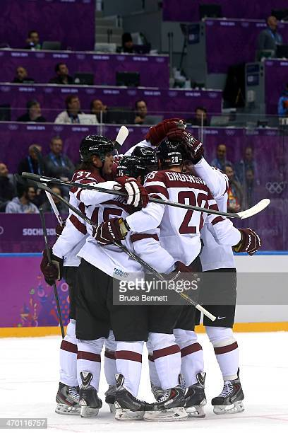 Lauris Darzins of Latvia celebrates with his teammates after scoring a goal in the first period against Jonas Hiller of Switzerland during the Men's...