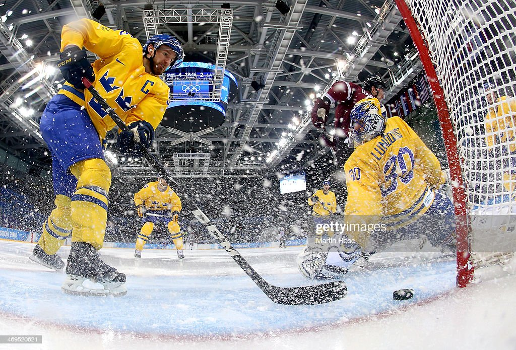 Lauris Darzins #10 of Latvia shoots against Niklas Kronwall #55 and Henrik Lundqvist #30 of Sweden in the second period during the Men's Ice Hockey Preliminary Round Group C game on day eight of the Sochi 2014 Winter Olympics at Shayba Arena on February 15, 2014 in Sochi, Russia.