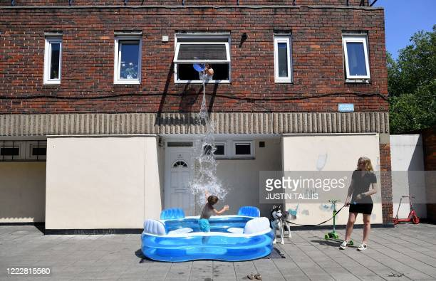 Laurita holds the family dog Lazer as her mum Kamila fills up a paddling pool by throwing water from an upstairs window over fiveyearold Luca as he...