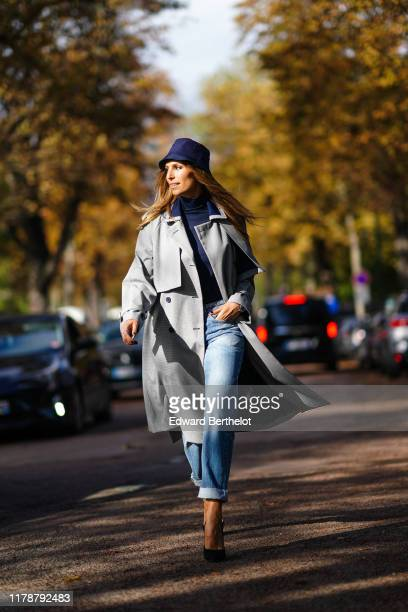 Laury Thilleman wears a blue bob hat a gray trench coat a blue turtleneck top blue denim jeans black pointy shoes outside Lacoste during Paris...
