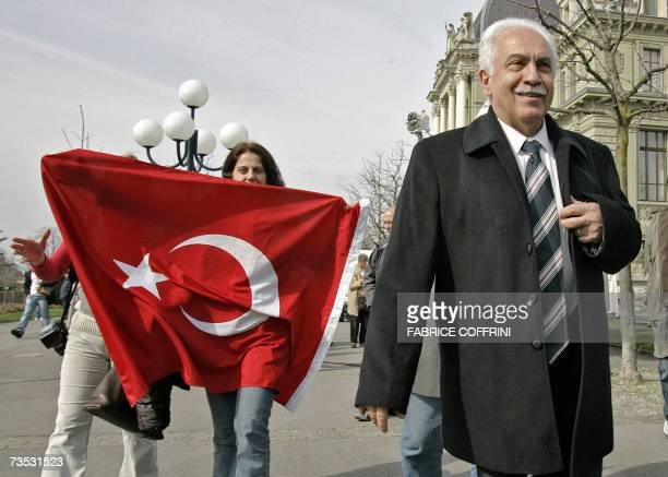 Turkish Workers' Party leader Dogu Perincek leaves the tribunal with supporters holding a Turkish flag after a court found him guilty of denying the...