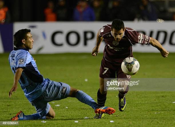 Lautaro Acosta of Lanús leaves Gerardo Yecerotte of Bolívar behind during a second leg quarter final match between Bol'ívar and Lanúœs as part of...