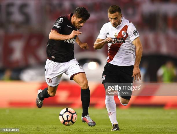 Lautaro Acosta of Lanus fights for the ball with Marcelo Saracchi of River Plate during a first leg match between River Plate and Lanus as part of...