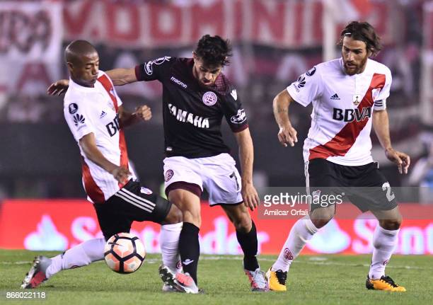 Lautaro Acosta of Lanus fights for the ball with Nicolas De La Cruz and Leonardo Ponzio of River Plate during a first leg match between River Plate...