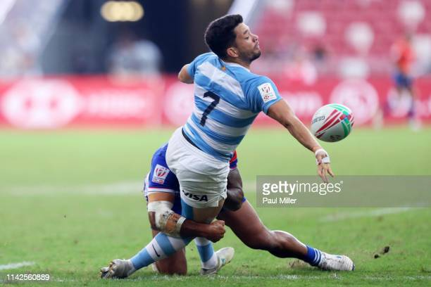 Lautaro Bazan Velez of Argentina hands off the ball during the 5th place semi final between Samoa and Argentina on day two of the HSBC Rugby Sevens...