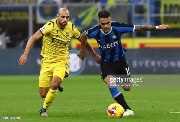 Lautaro Martinez of FC Internazionale competes for the ball with Sofyan Amrabat of Hellas Verona during the Serie A match between FC Internazionale...