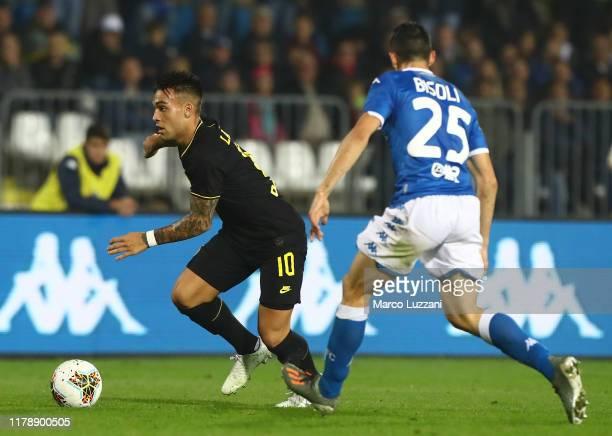 Lautaro Martinez of FC Internazionale is challenged by Dinitri Bisoli of Brescia Calcio during the Serie A match between Brescia Calcio and FC...