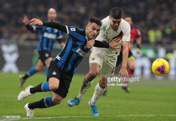 Lautaro Martinez of FC Internazionale is challenged by Gianluca Mancini of AS Roma during the Serie A match between FC Internazionale and AS Roma at...