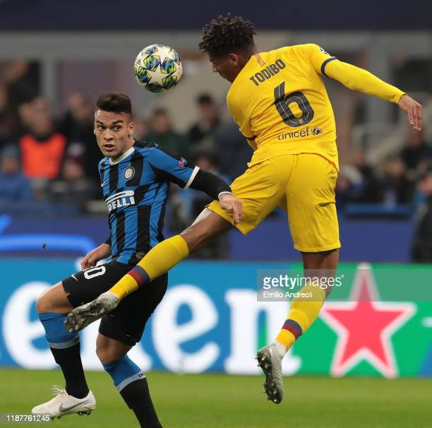 Lautaro Martinez of FC Internazionale jumps for the ball against Jean-Clair Todibo of FC Barcelona during the UEFA Champions League group F match...