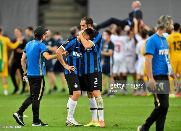 Lautaro Martinez of Inter Milan is consoled by Diego Godin of Inter Milan following their team's defeat in the UEFA Europa League Final between...