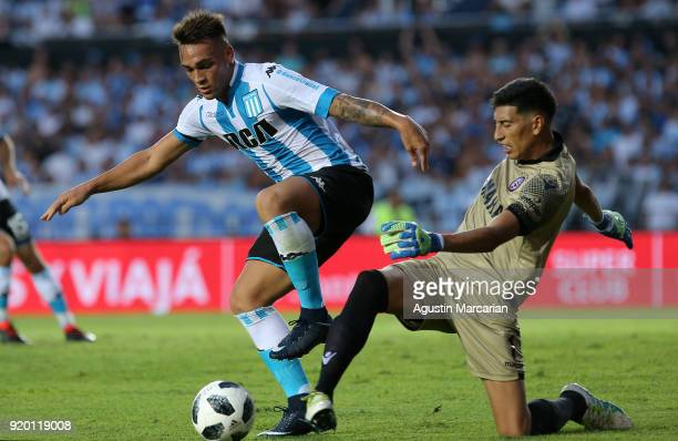 Lautaro Martinez of Racing Club fights for the ball with Esteban Andrada goalkeeper of Lanus during a match between Racing Club and Lanus as part of...