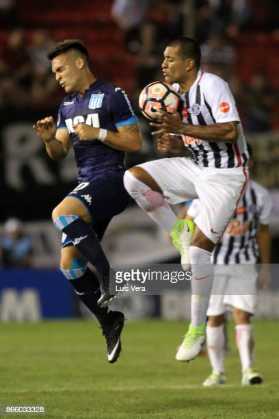 Lautaro Martinez of Racing Club fights for the ball with Paulo Da Silva of Libertad during a first leg match between Libertad and Racing Club as part...