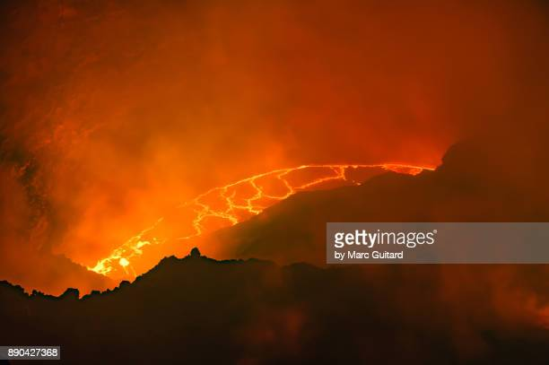 lava and smoke thrash inside the crater of erta ale, an extremely active shield volcano located in the danakil depression in the afar region of ethiopia - shield volcano stock pictures, royalty-free photos & images