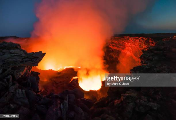 lava and smoke thrash inside the crater of erta ale, an extremely active shield volcano located in the danakil depression in the afar region of ethiopia - hell stock pictures, royalty-free photos & images