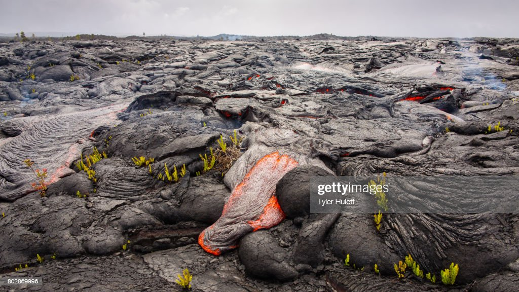 Lava destroys a landscape under cloudy skies : Stock Photo