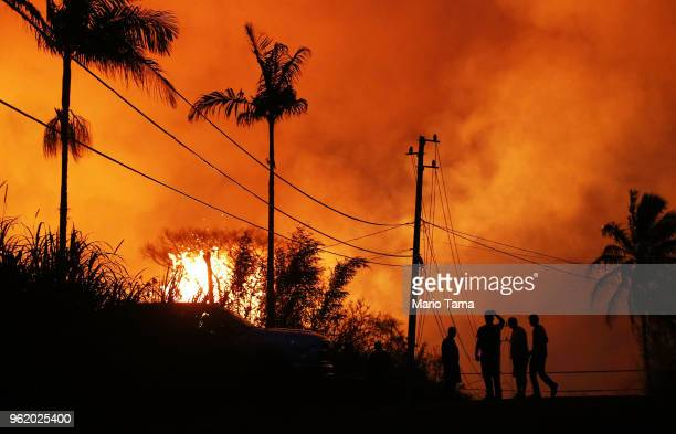 Lava erupts from a Kilauea volcano fissure as people gather on a residential street in Leilani Gardens on Hawaii's Big Island on May 23 2018 in Pahoa...