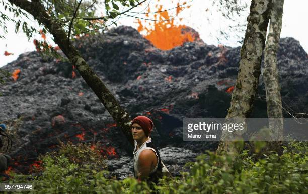 A lava fissure erupts as a resident stands nearby in the aftermath of eruptions from the Kilauea volcano on Hawaii's Big Island on May 12 2018 in...