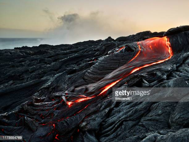 lava flowing from pu'u o'o' at hawaii volcanoes national park against sky - volcanic rock stock pictures, royalty-free photos & images