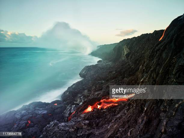 lava flowing from pu'u o'o' in sea at hawaii volcanoes national park against sky - hawaii volcanoes national park stock pictures, royalty-free photos & images