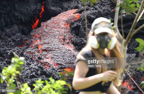 Lava flows at a new fissure in the aftermath of eruptions from the Kilauea volcano on Hawaii's Big Island as a local resident walks nearby after...