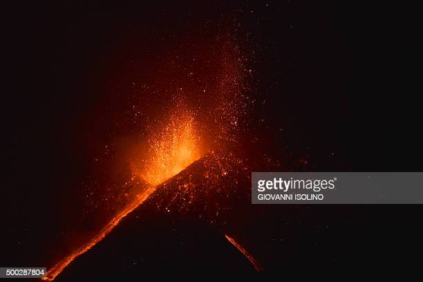 Lava flows from the Mount Etna volcano on the southern Italian island of Sicily near Catania on December 6 2015 at night The volcano on the...