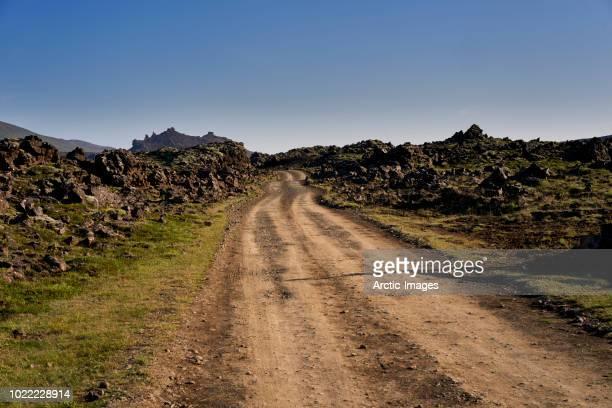 lava formations and unpaved road, western iceland - schotterstrecke stock-fotos und bilder