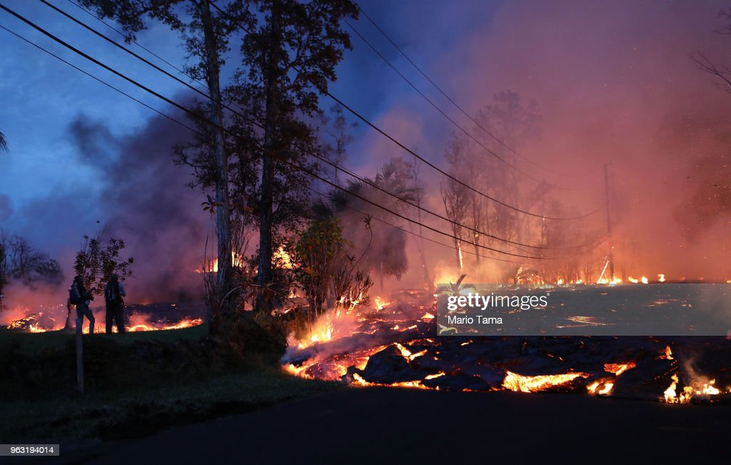 Lava from a Kilauea volcano fissure advances up a residential street in Leilani Estates, on Hawaii's Big Island, on May 27, 2018 in Pahoa, Hawaii. Lava from the volcano also flowed to a geothermal power plant today raising fears that toxic gas could be released if wells are breached by lava. The Big Island, one of eight main islands that make up Hawaii state, is struggling with tourist bookings following the Kilauea volcano eruptions, with summer bookings at the island down 50 percent. Officials stress that the eruptions have thus far only affected a small portion of the island.