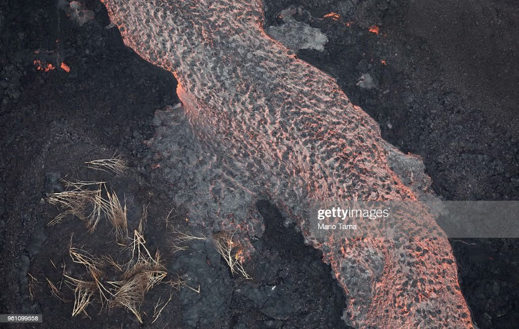 Lava from a Kilauea volcano fissure flows past downed trees towards the Pacific Ocean, on Hawaii's Big Island, on May 21, 2018 near Pahoa, Hawaii. Officials are concerned that 'laze', a dangerous product produced when hot lava hits cool ocean water, will affect residents. Laze, a word combination of lava and haze, contains hydrochloric acid steam along with volcanic glass particles.