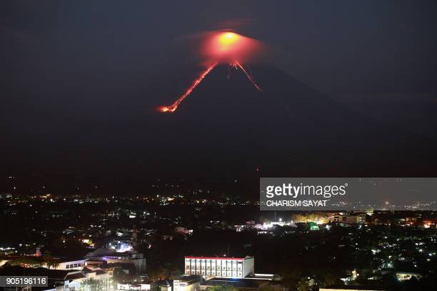 TOPSHOT Lava from Mayon volcano is seen as it erupts in Legazpi on January 15 2018 The Philippines raised the alert level for the country's most...