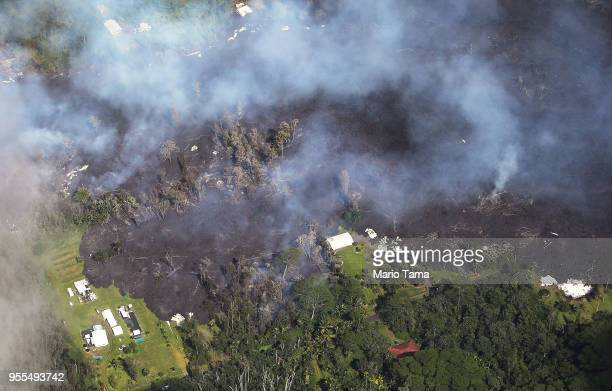 Lava from volcanic fissures slowly flows as structures and trees burn in the Leilani Estates neighborhood in the aftermath of eruptions from the the...