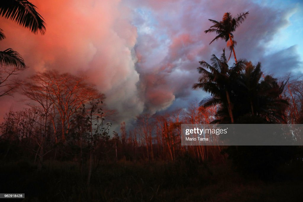 Lava glowing from a Kilauea fissure illuminates dying trees in Leilani Estates, on Hawaii's Big Island, on May 26, 2018 in Pahoa, Hawaii. The Big Island, one of eight main islands that make up Hawaii state, is struggling with tourist bookings following the Kilauea volcano eruptions, with summer bookings down 50 percent. Officials stress that the eruptions have thus far only affected a small portion of the island. Visitors spent $2.4 billion at the island in 2017.