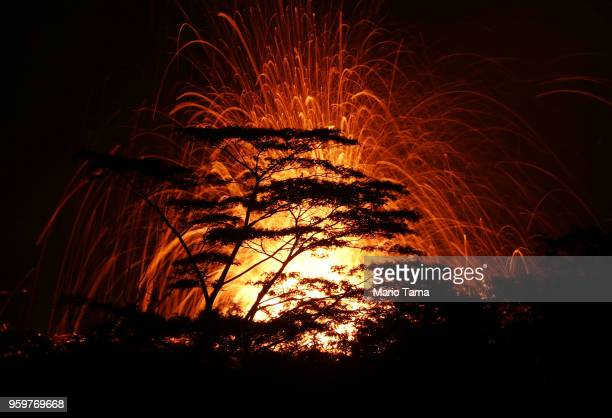 Lava is blurred as it erupts from a Kilauea volcano fissure above treetops on Hawaii's Big Island on May 17 2018 in Kapoho Hawaii The US Geological...