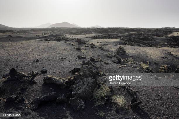 lava plain and distant volcanoes. - lava stock pictures, royalty-free photos & images