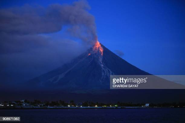 TOPSHOT Lava spews from the Mayon volcano as it continues to erupt seen from Legazpi City in Albay province south of Manila early on January 23 2018...