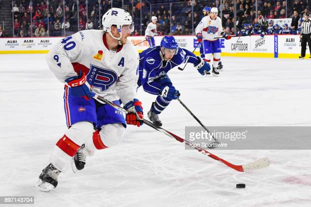 Laval Rocket defenceman Matt Taormina skates with the puck cwhile chased by Syracuse Crunch center Anthony Cirelli during the Syracuse Crunch versus...