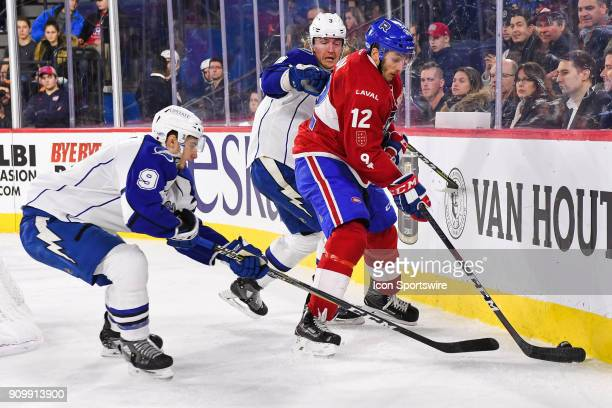 Laval Rocket left wing Kyle Baun tries to keep control of the puck while pressured by Syracuse Crunch center Anthony Cirelli and Syracuse Crunch...