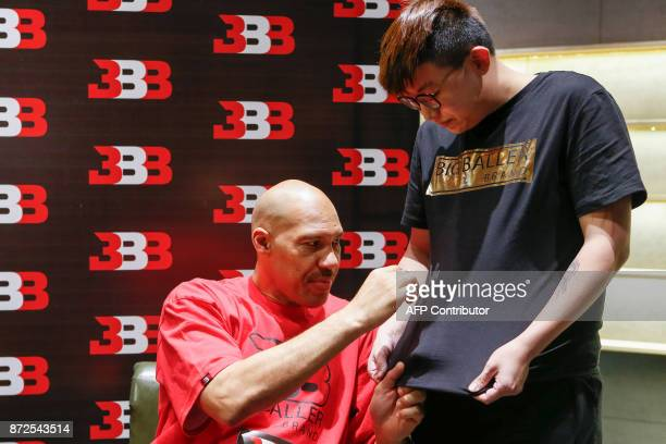 LaVar Ball father of LiAngelo Ball and the owner of the Big Baller brand signs a fan's Tshirt during a promotional event in Shanghai on November 10...