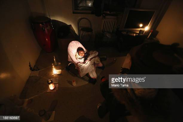 Lavell Harrington plays while shining a flashlight on baby Selena in their apartment lit with candles and without power or water in the Jacob Riis...