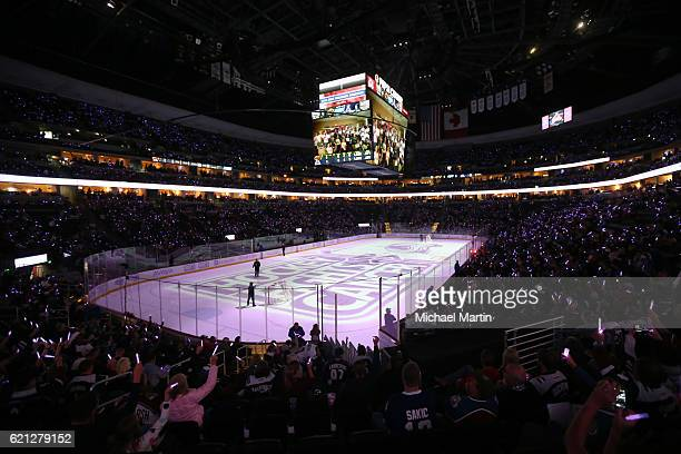 Lavender glow sticks illuminate the arena during the glow stick ceremony as part of the Hockey Fights Cancer game between the Colorado Avalanche and...