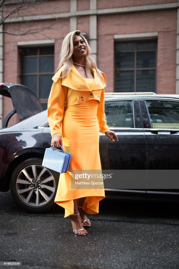 Laverne Cox is seen on the street attending Christian Siriano during New York Fashion Week wearing a yellow dress with blue bag on February 10, 2018 in New York City.