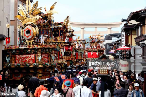 Lavishly decorated floats are lined up on a street leading to Hachiman Jinja Shrine as spectators watch on October 10 2017 in Takayama Gifu Japan The...