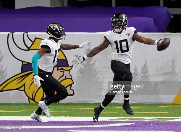 Laviska Shenault Jr. #10 of the Jacksonville Jaguars celebrates his touchdown with teammate D.J. Chark in the first quarter against the Minnesota...