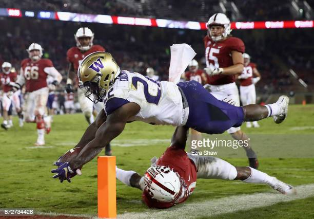 Lavon Coleman of the Washington Huskies dives over Justin Reid of the Stanford Cardinal to try to score a touchdown at Stanford Stadium on November...