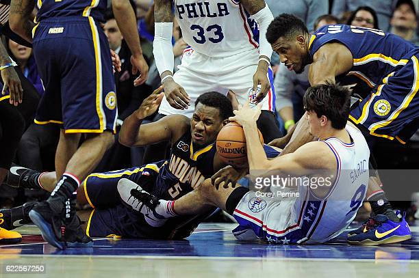 Lavoy Allen of the Indiana Pacers battles for the ball from Dario Saric of the Philadelphia 76ers as Thaddeus Young of the Indiana Pacers tries to...