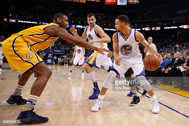 Lavoy Allen of the Indiana Pacers guards Stephen Curry of the Golden State Warriors as he looks to pass to Andrew Bogut of the Golden State Warriors...