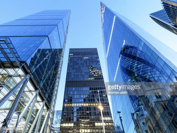 law angle view of futuristic london skyscrapers - multiple exposure - wolkenkrabber stockfoto's en -beelden