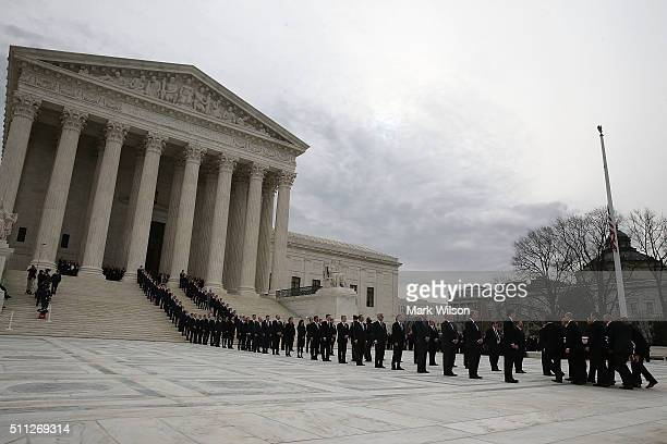 Law clercks past and present line the steps as the casket of Associate Justice Antonin Scalia is carried by US Supreme Court police officers up the...